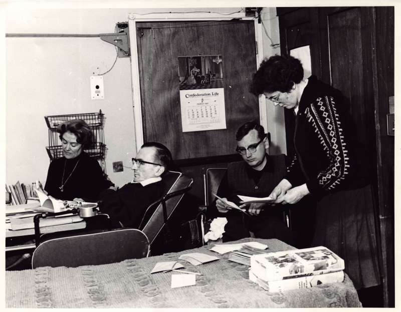 A group of people in an editorial office working on documents and letters