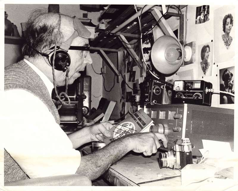 An older man wearing headphones sat at a desk with various amateur radio broadcasting equipment