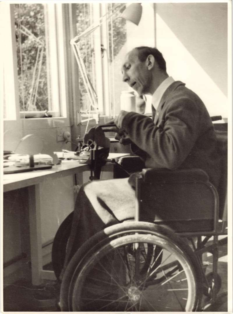 A man in a wheelchair at a workbench working on a piece of wood in a clamp