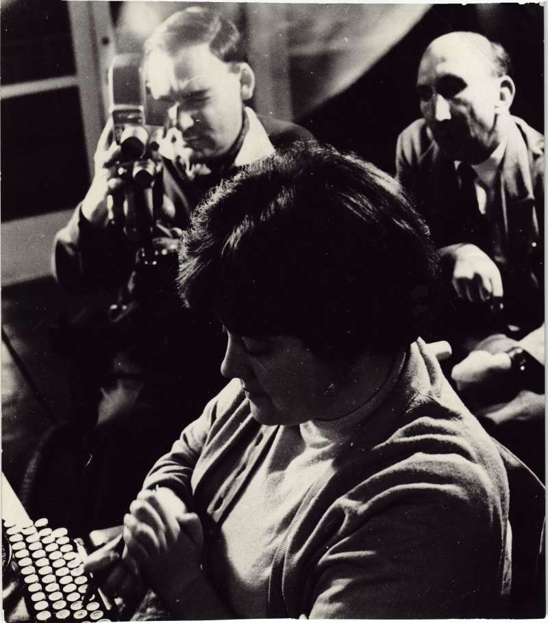 A woman in front of a typewriter being filmed by a man in a wheelchair, with another man looking on