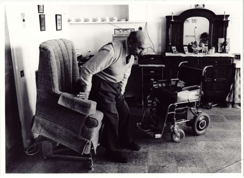 An older man moving from a tilted armchair into a wheelchair