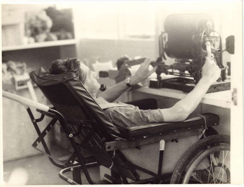 A man in a wheelchair leaning back to use an old printing machine