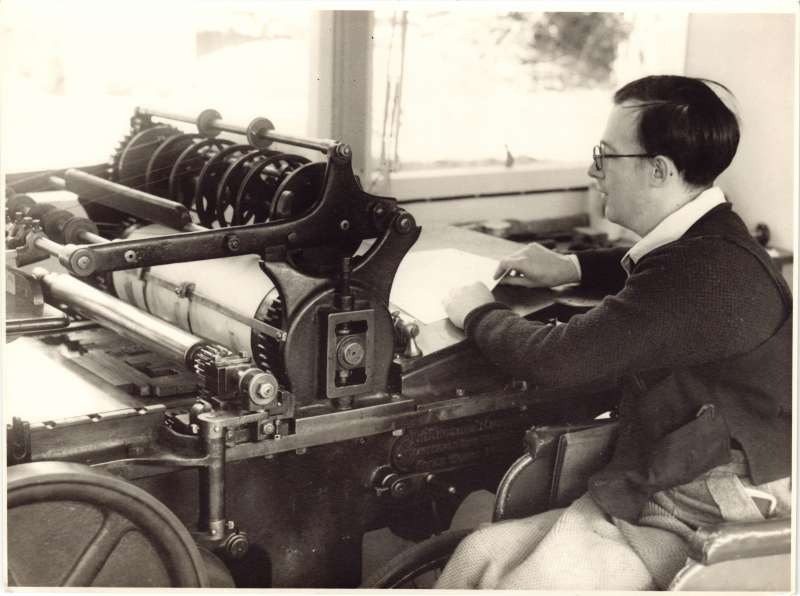 A man in a workroom using a large old duplicating machine
