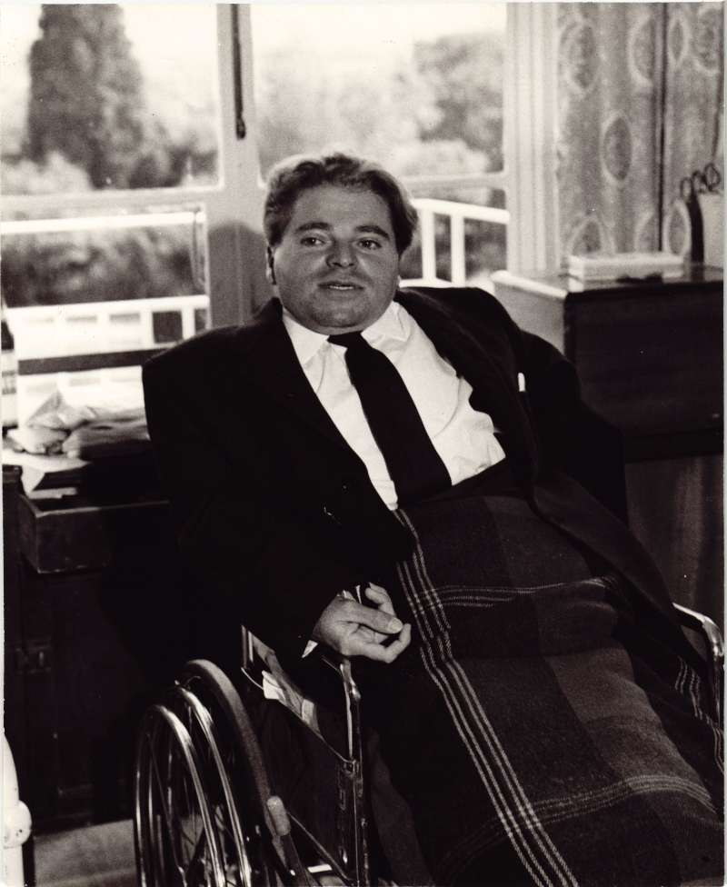 A man dressed in a smart jacket and tie sitting in a wheelchair with a blanket on his lap