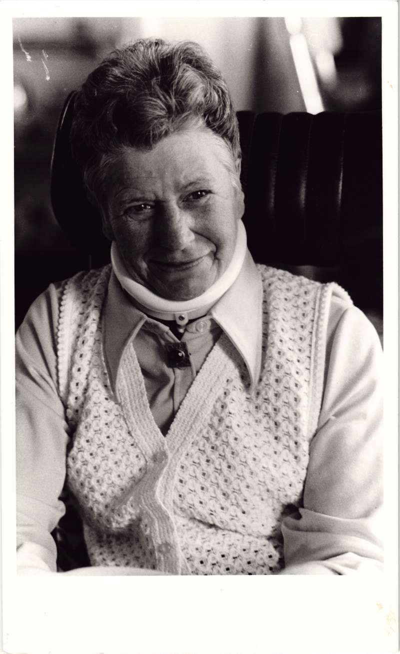 A close up of a woman wearing a light coloured knitted waistcoat and a white supportive neck collar