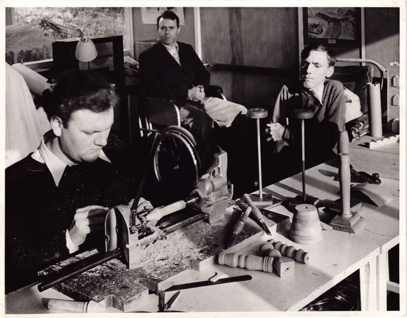 A man covered in sawdust working on a lathe making parts for a castle with two others watching on