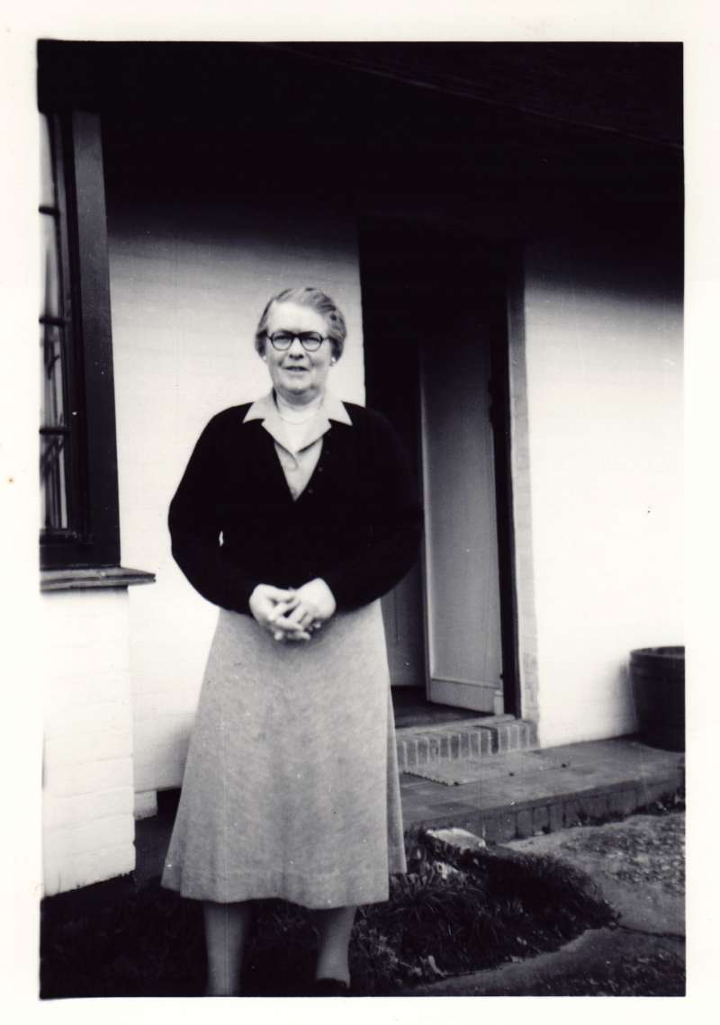 An older woman in glasses standing by some steps outside a doorway