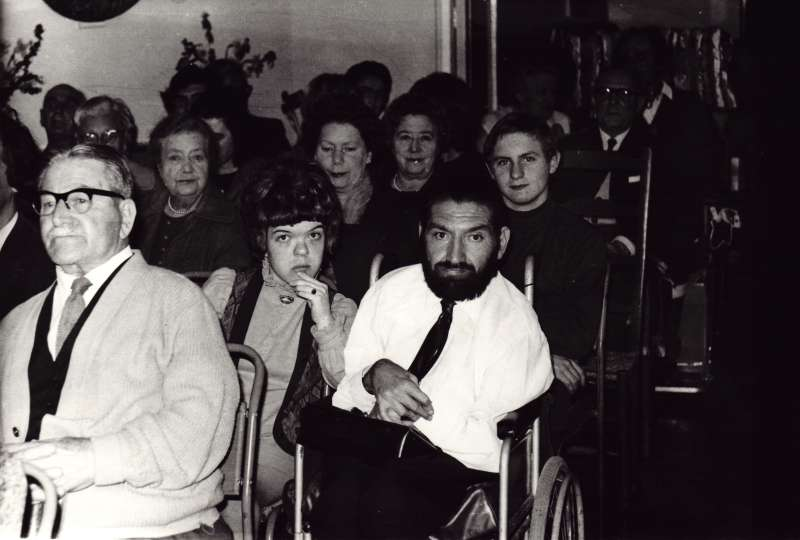 A group of people in seats and wheelchairs gathered for an event inside Le Court