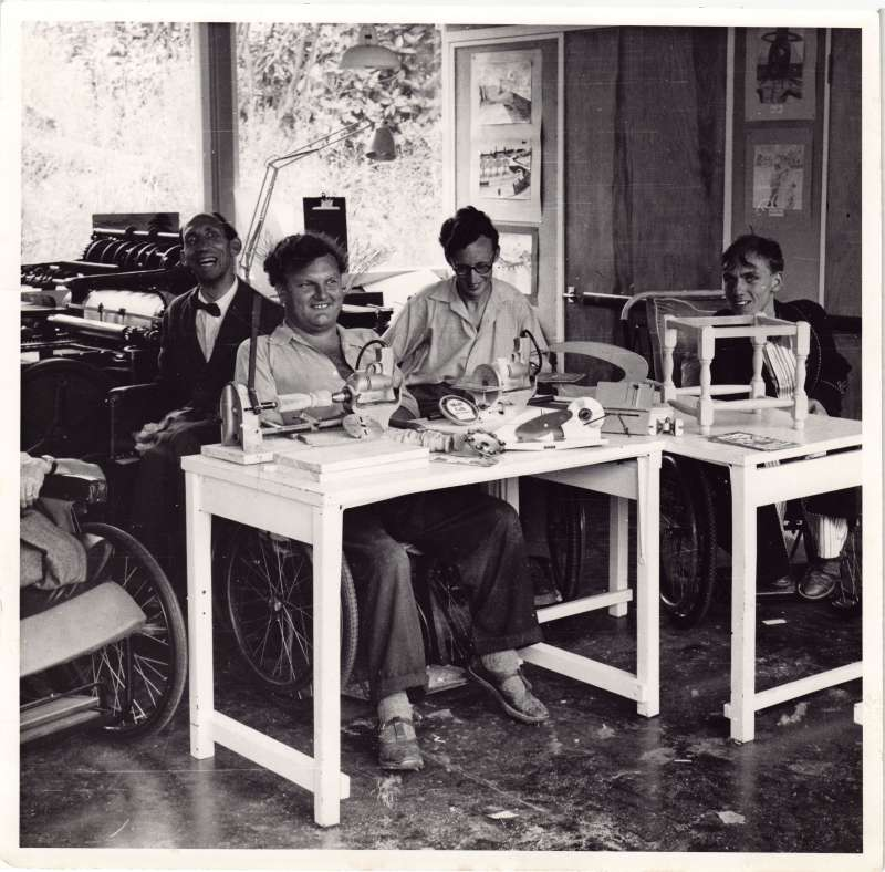 Four men in wheelchairs in a workshop with various equipment smiling at the camera