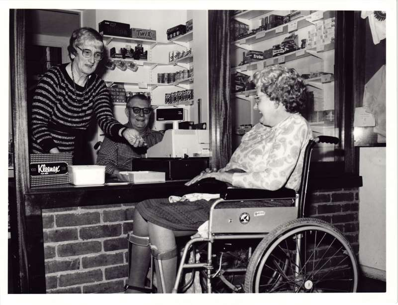 A woman standing behind a counter with a man in a wheelchair, serving a woman buying something from a tuck shop