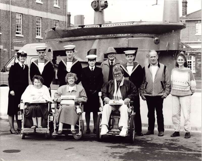 Two women and a man in wheelchairs in a group shot with several young sailors and three volunteers