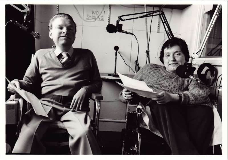 A man and a woman in a recording studio, recording from documents they are holding.