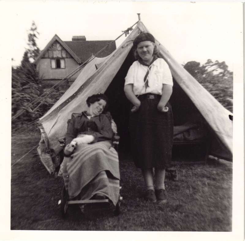 Two women outside a tent, one in a wheelchair, one standing in a Girl Guides uniform