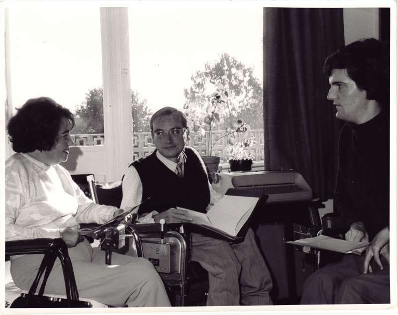 Two men and a woman in wheelchairs talking and looking at documents in a room by a window