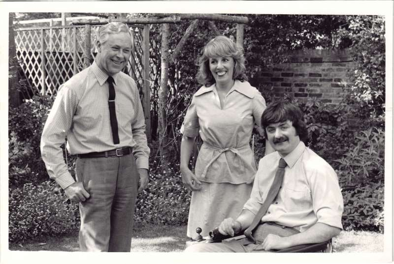 A young man in a motorised wheelchair with Esther Rantzen and another man smiling at the camera