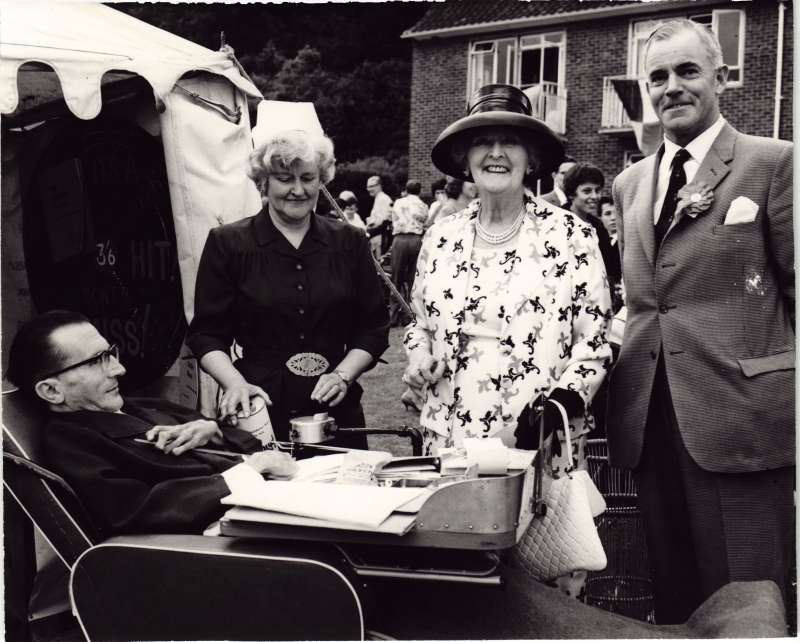 A man in a wheelchair outside a marquee with a man and two women