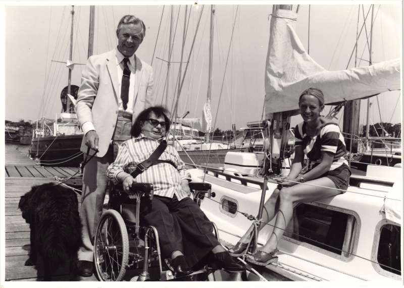 A man in a wheelchair being pushed by a man holding a dog, next to a yacht talking to a young woman