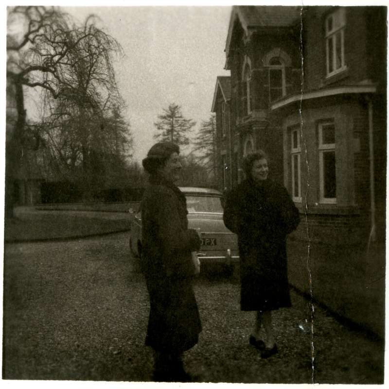 Two women in long coats standing outside a building with a car behind them