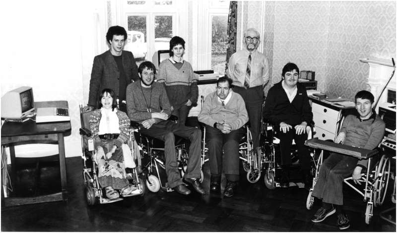 Five people in wheelchairs and three others standing in a room with computers in the background