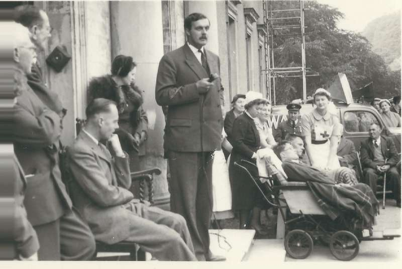 Group of people outside, including Leonard Cheshire, listening to a man speaking into a microphone