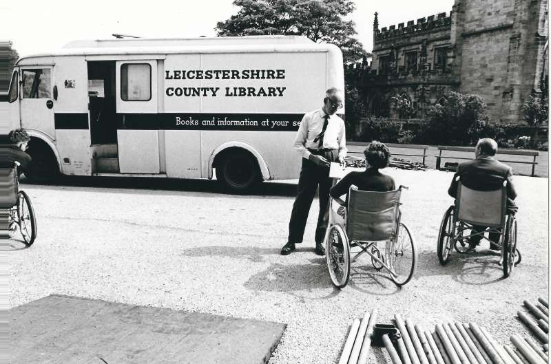 A mobile library parked outside Staunton Harold with staff offering books to residents