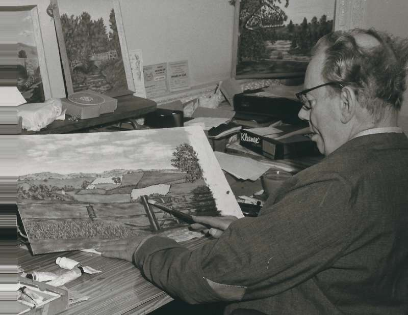 A man at a desk painting a countryside landscape
