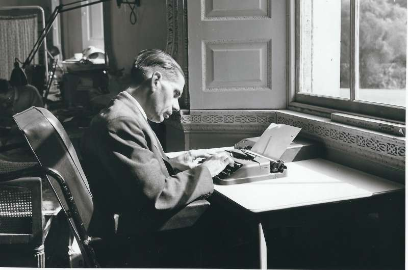 A man at a desk in front of a window typing on a typewriter