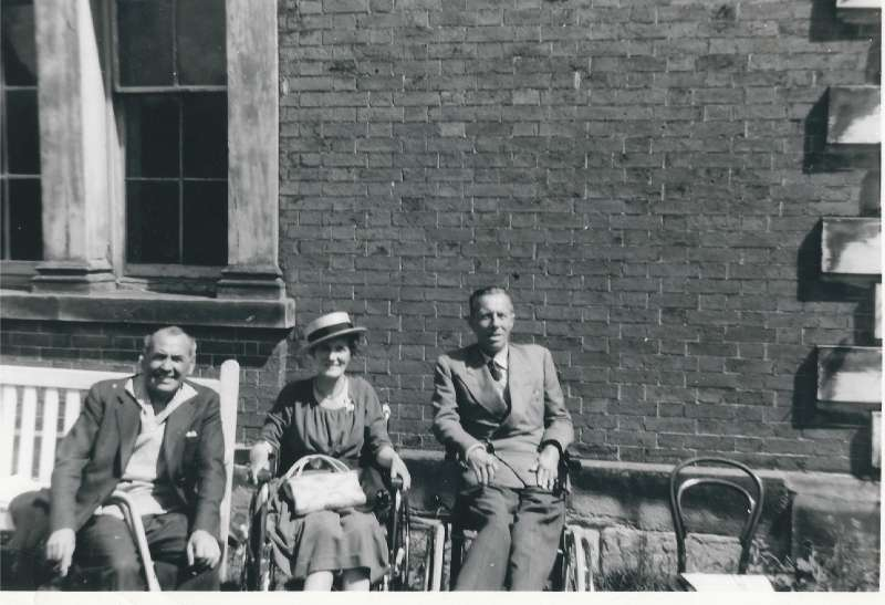 Two men and a woman sitting outside with Staunton Harold Hall behind them