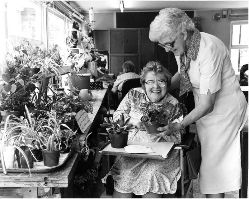 A smiling lady in a wheelchair holding two pot plants, sat next to a plant bench, with a lady helping her
