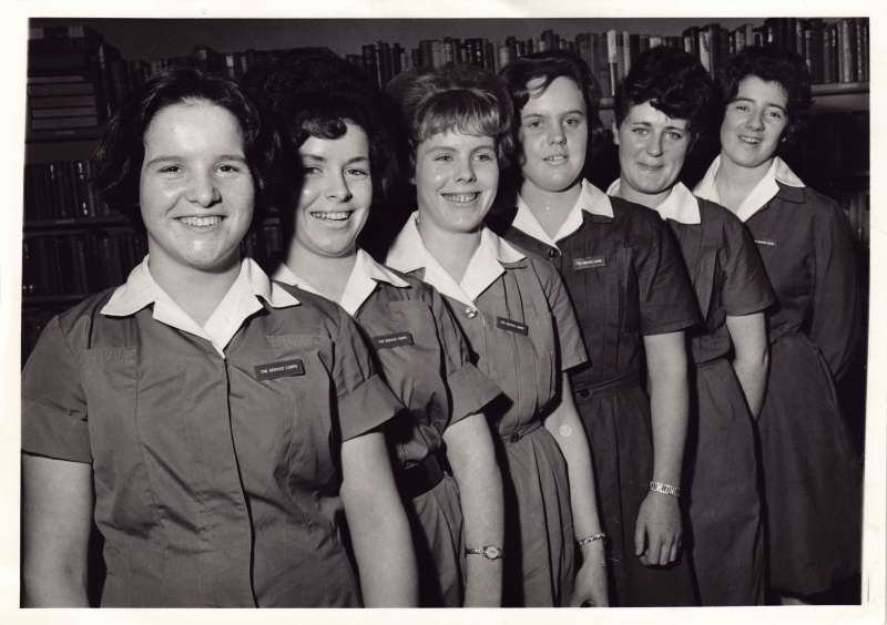 Six young women in nursing uniforms lined up in a posed photo