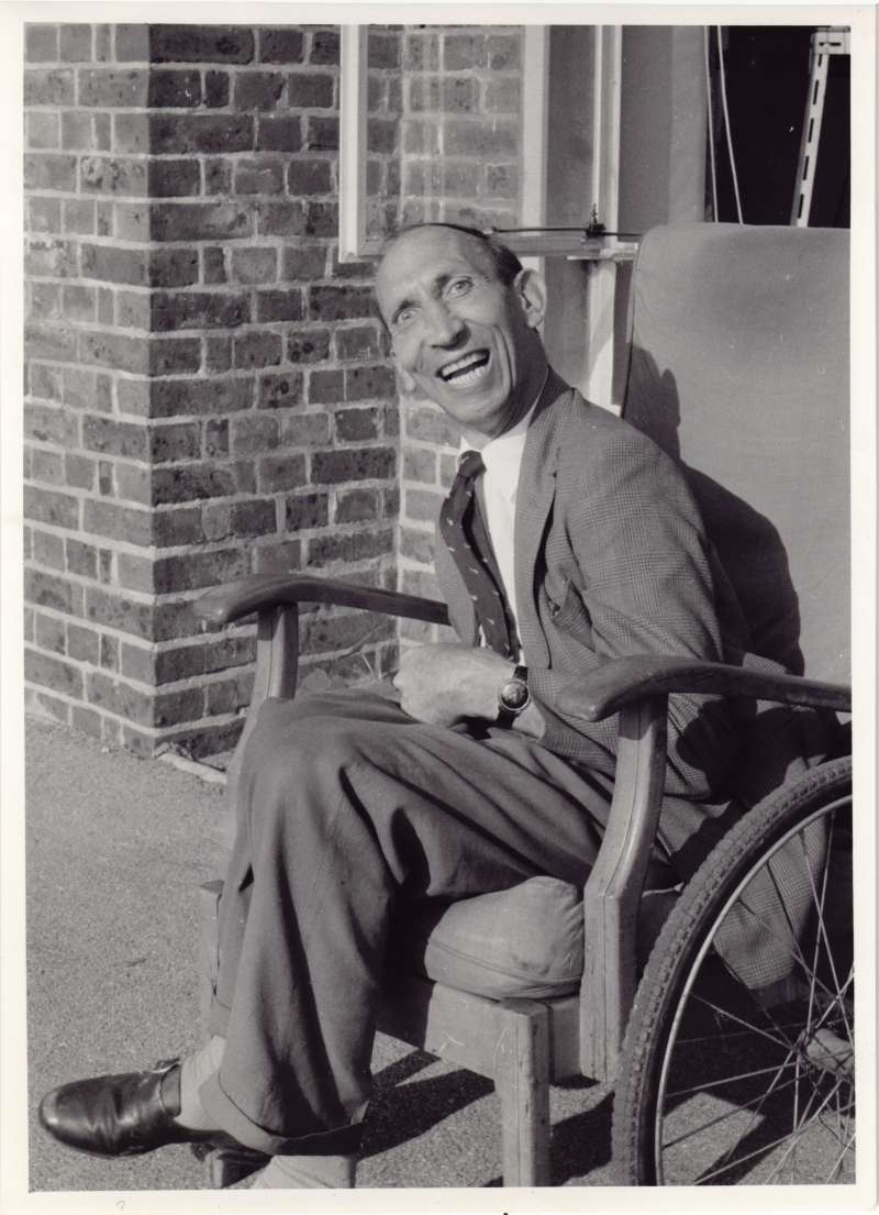 A smiling man sitting in an armchair outside