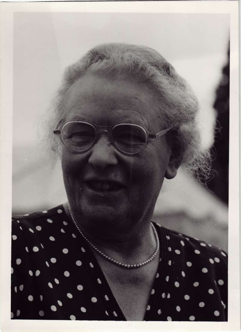 Close up photo of a lady in a polka dot dress wearing glasses and a necklace
