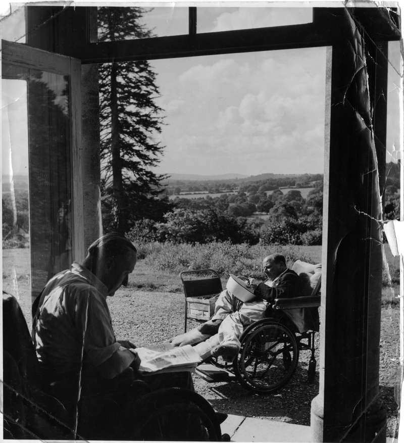 Two men in wheelchairs, one reading a newspaper, one shelling peas with a tree and fields in the background