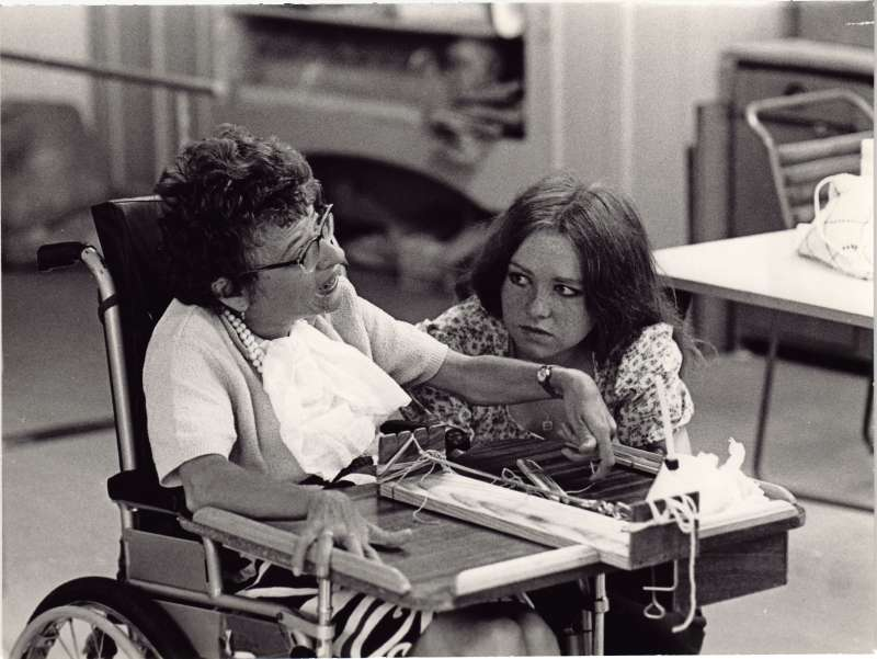 Woman in wheelchair weaving, with a young woman crouched next to her watching on
