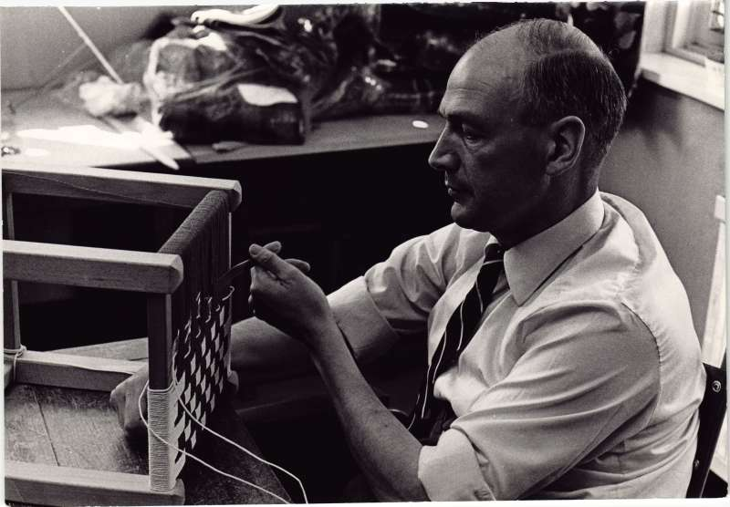 A close up of a man weaving a seat for a stool