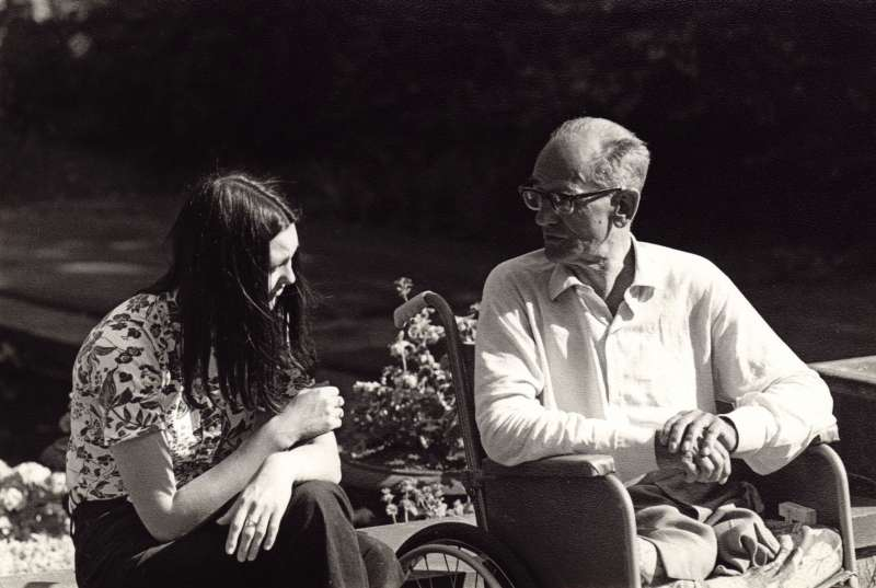 An older man in a wheelchair outside talking with a young woman sat next to him