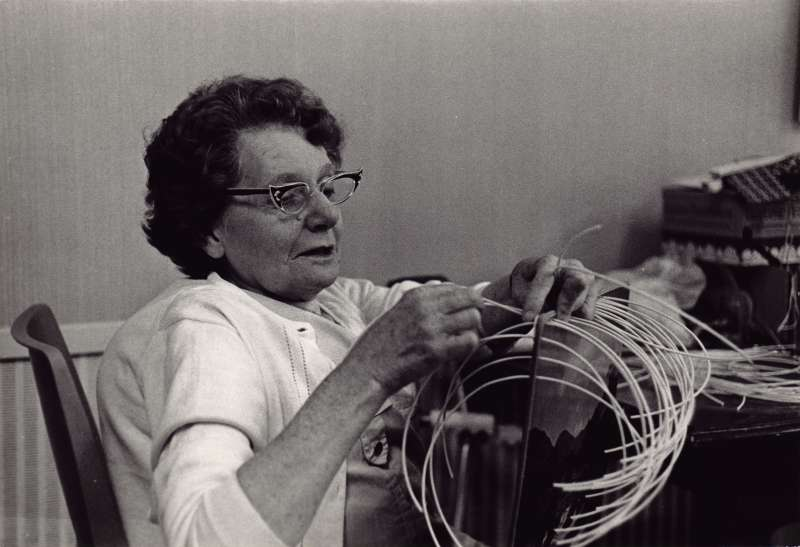 A close up of an older woman wearing glasses making a basket