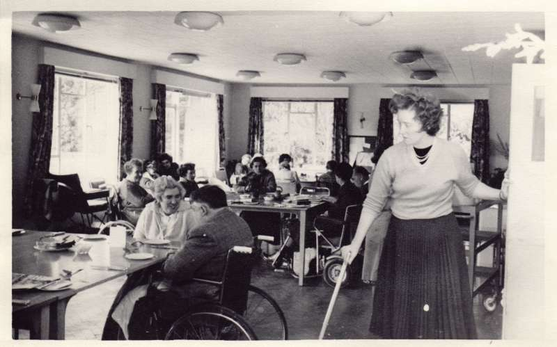 A lady standing with a walking stick in the foreground with residents in wheelchairs sat at dining tables behind