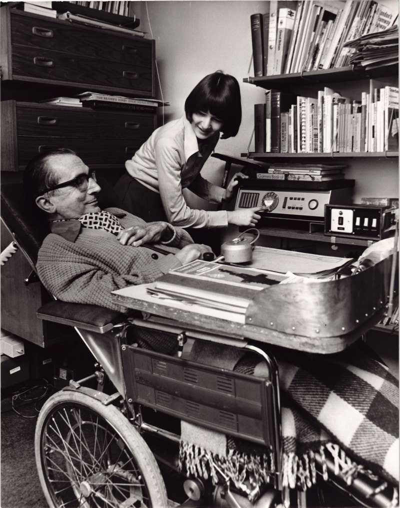 Woman helping a man in a wheelchair to use a specially adapted telephone
