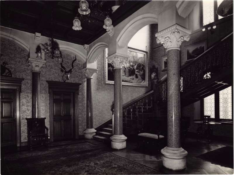 Photo showing a grand staircase, paintings and pillars inside the entrance at Le Court