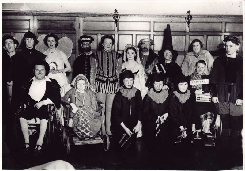 Group of people in fancy dress, some in wheelchairs, in a posed photo