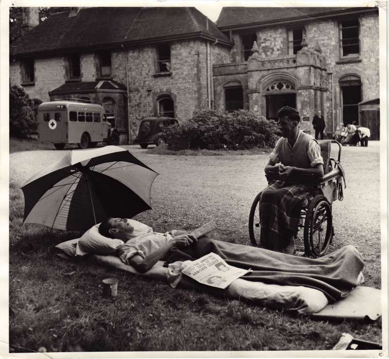 A man lying on the ground talking to another man in a wheelchair, with the old Le Court house in the background