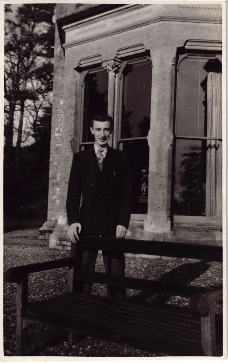 Young man standing by a bench in front of a window at the old Le Court
