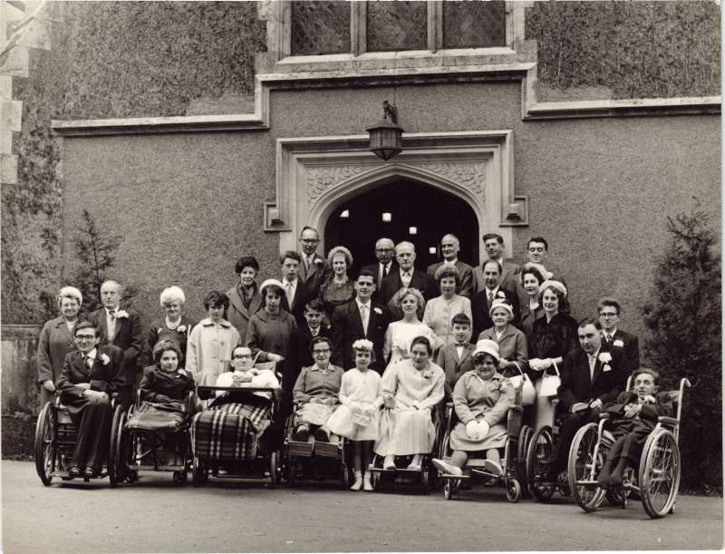 Group of people, some in wheelchairs, posed for a wedding photo