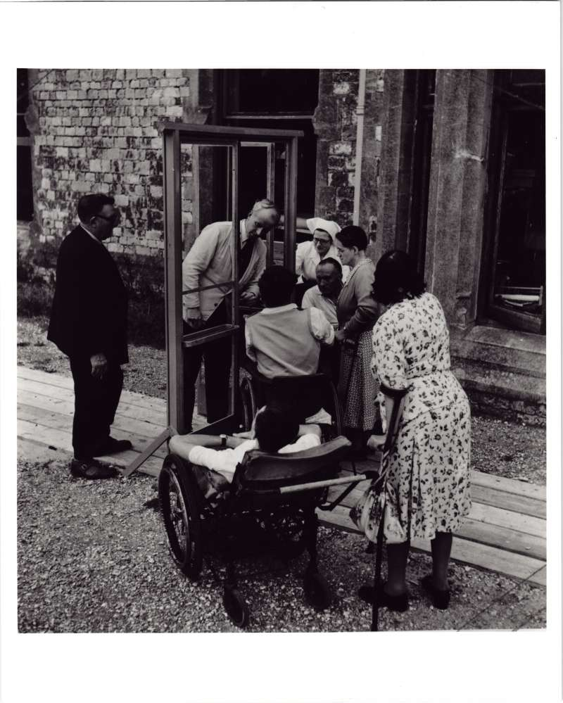 Group of people outside, two in wheelchairs, measuring a sample door frame to fit wheelchairs through