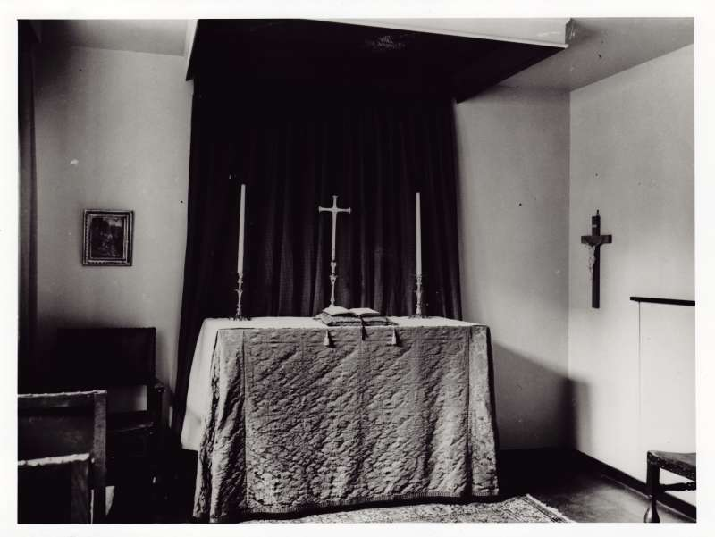 Photo showing the inside of a chapel, with an alter table and cross on the wall