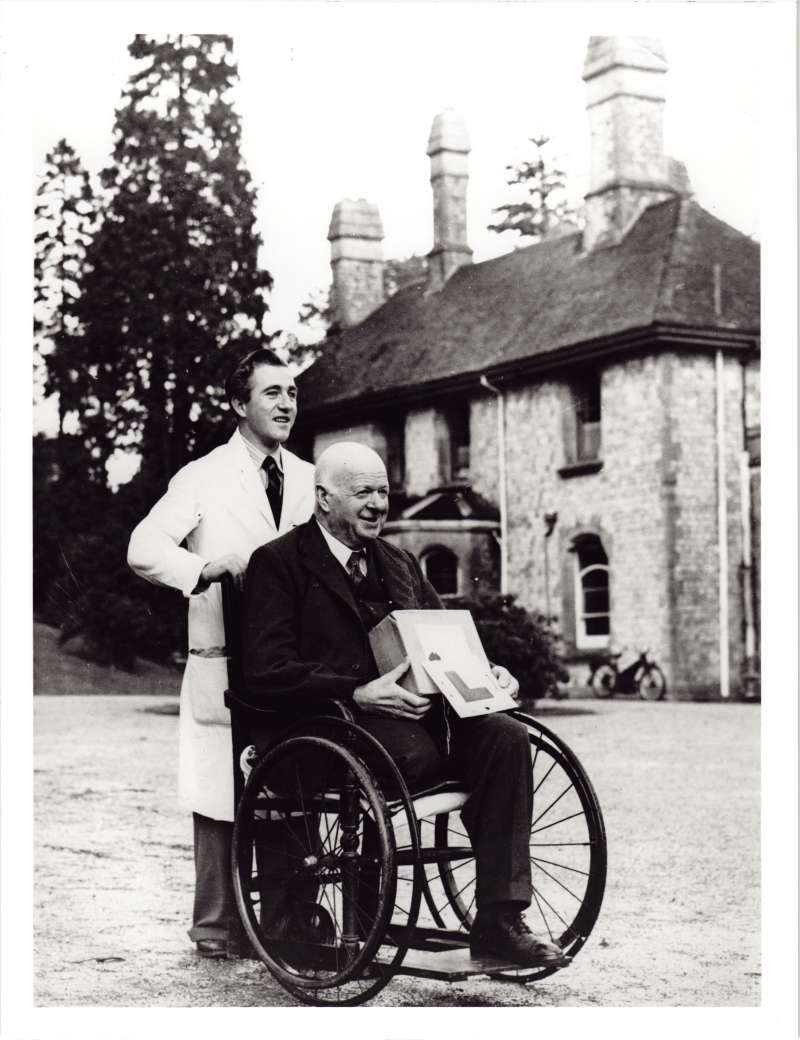 A man in a white coat standing behind a man in a wheelchair who is holding a box on his lap