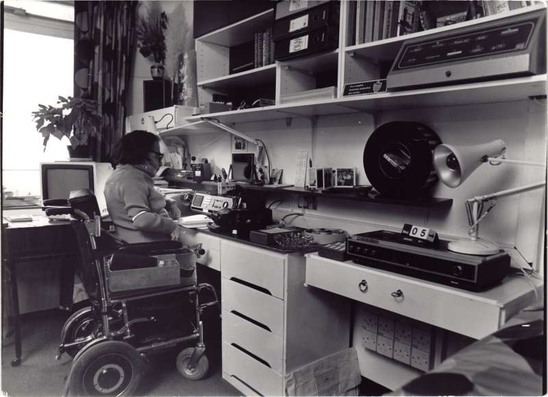 A man in a wheelchair sitting in front of various film recording equipment