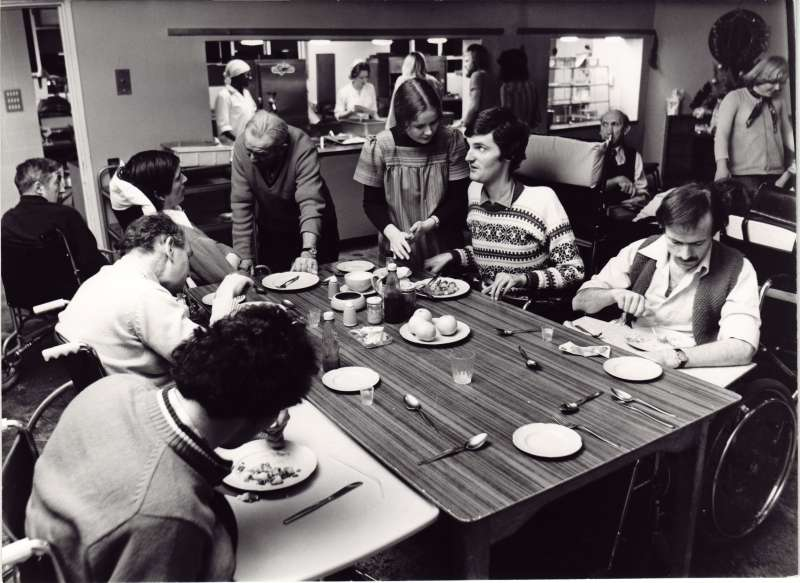 Six people around a table in the dining room eating, with the kitchen and catering staff in the background