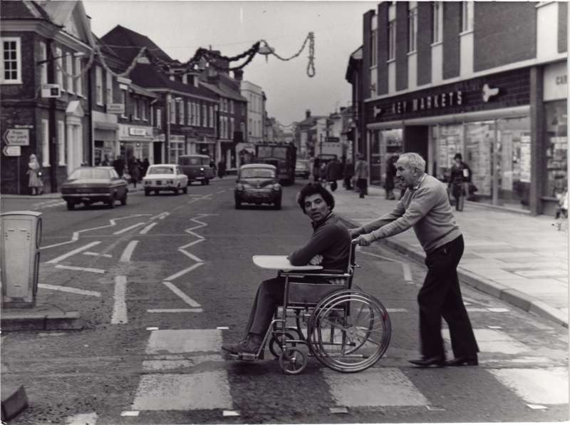 A man pushing another man in a wheelchair across a pedestrian crossing with shops in the background